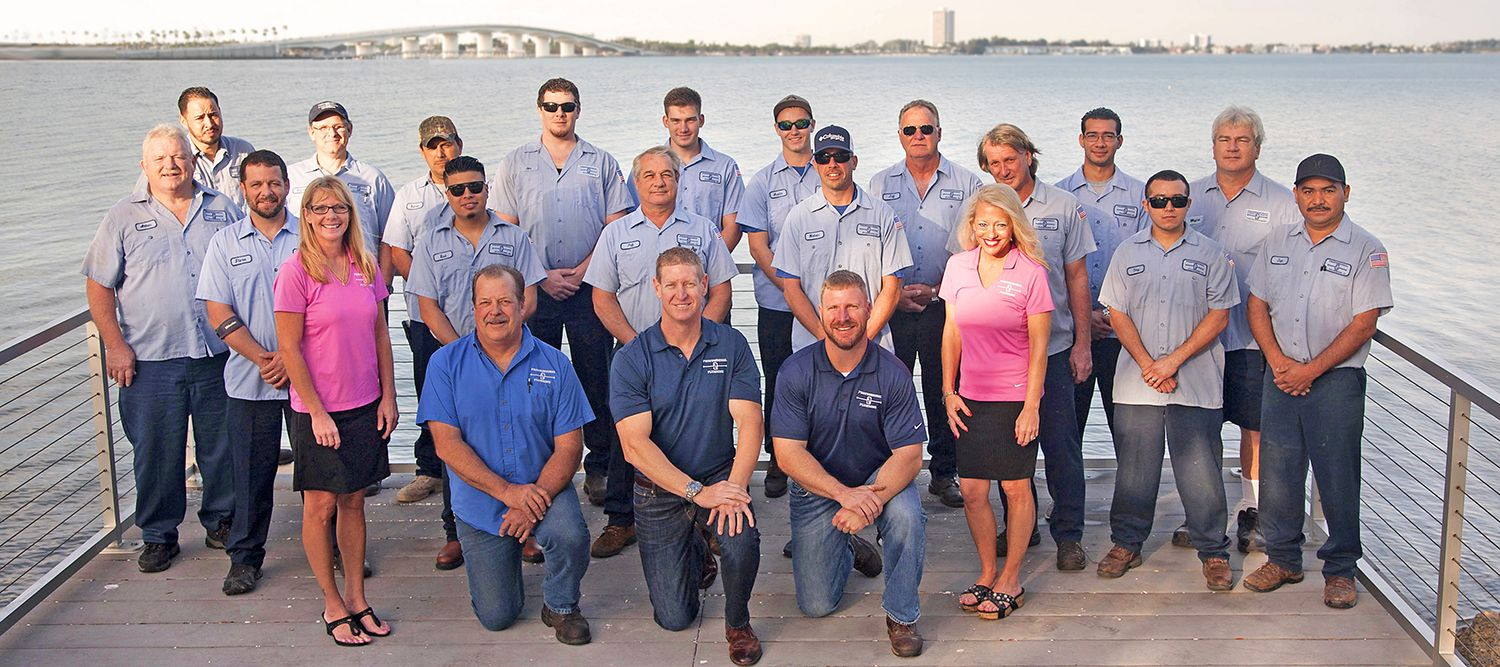 The Professional Plumbing & Design team with the Ringling Causeway and Sarasota Bay in the background.